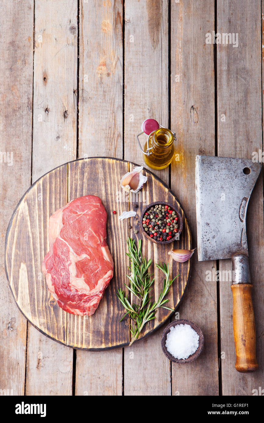 Raw fresh meat Steak with salt and pepper, rosemary and tomatoes on cutting board Copy space. Top view - Stock Image