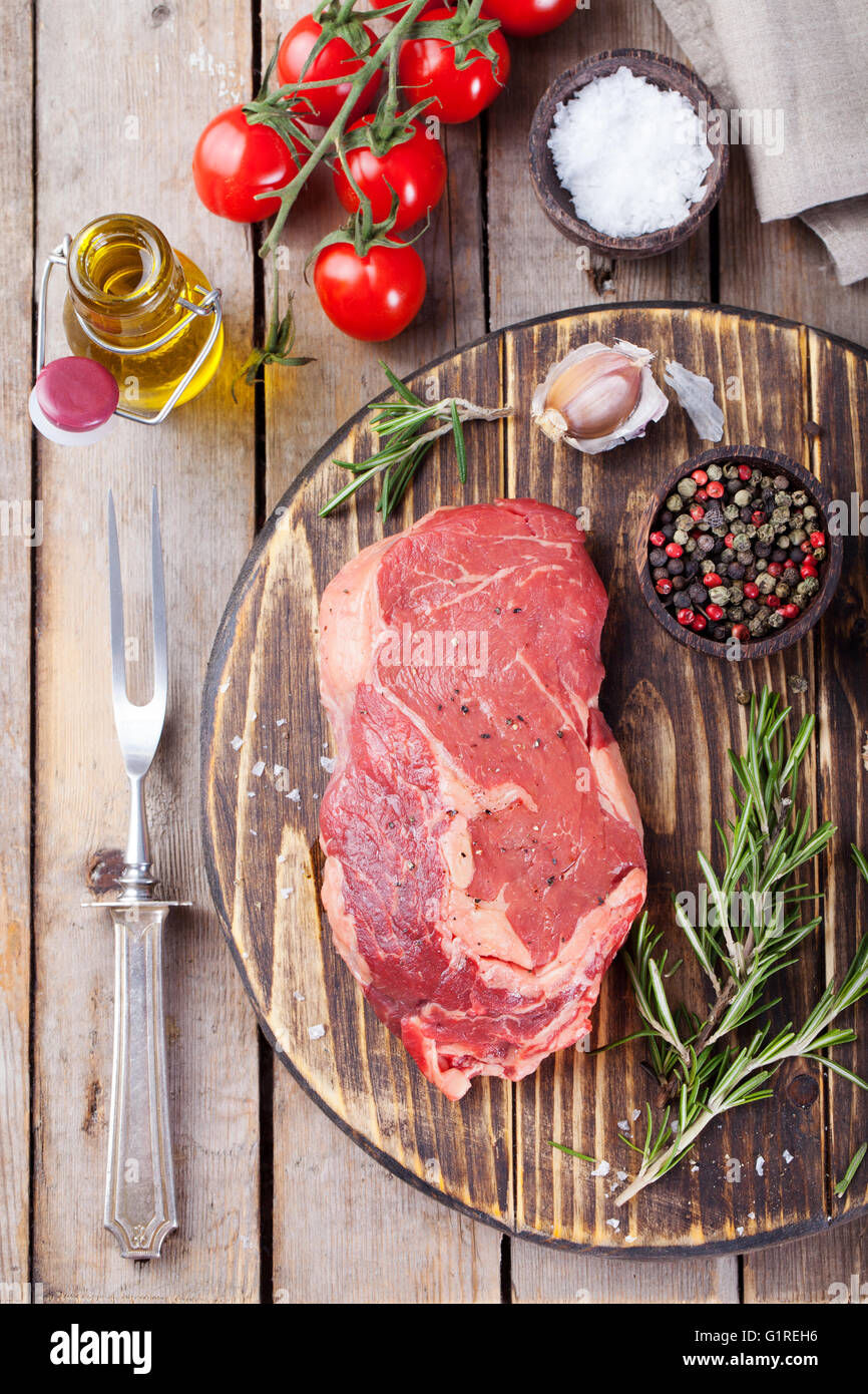 Raw fresh meat Steak with salt and pepper, rosemary and tomatoes on cutting board on dark wooden background Top - Stock Image