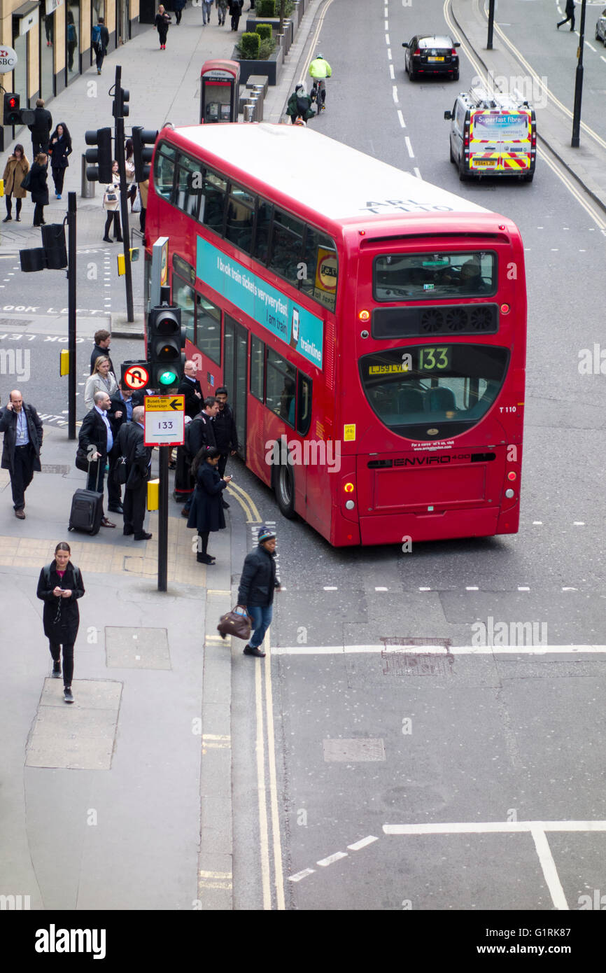 London bus turning left at a junction next to pedestrians on the pavement - Stock Image