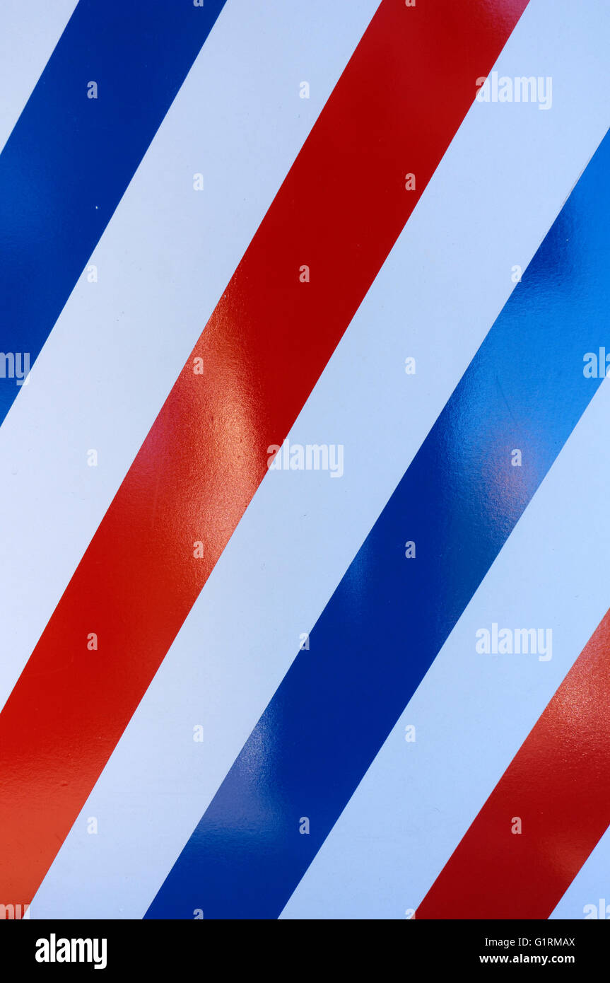 Close up of a striped red, white and blue barber shop background pattern - Stock Image