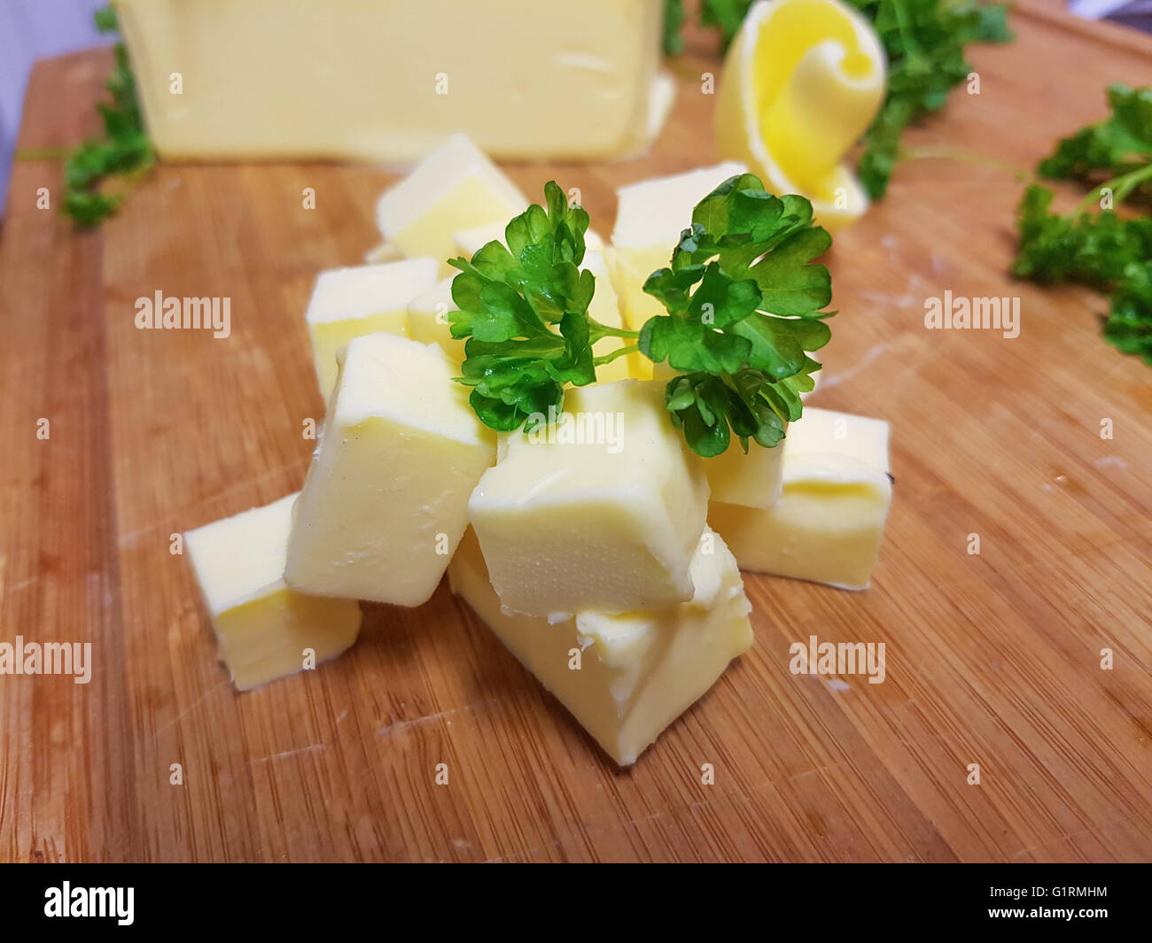 Pile of fresh, yellow butter cubes, on a wooden cutting board Stock Photo