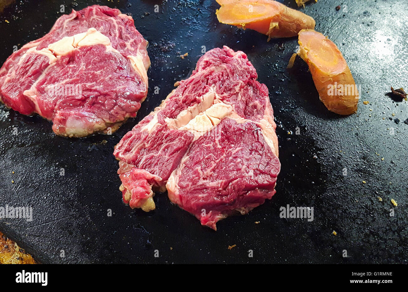 Frying raw black angus entrecote meat, on a frying table Stock Photo