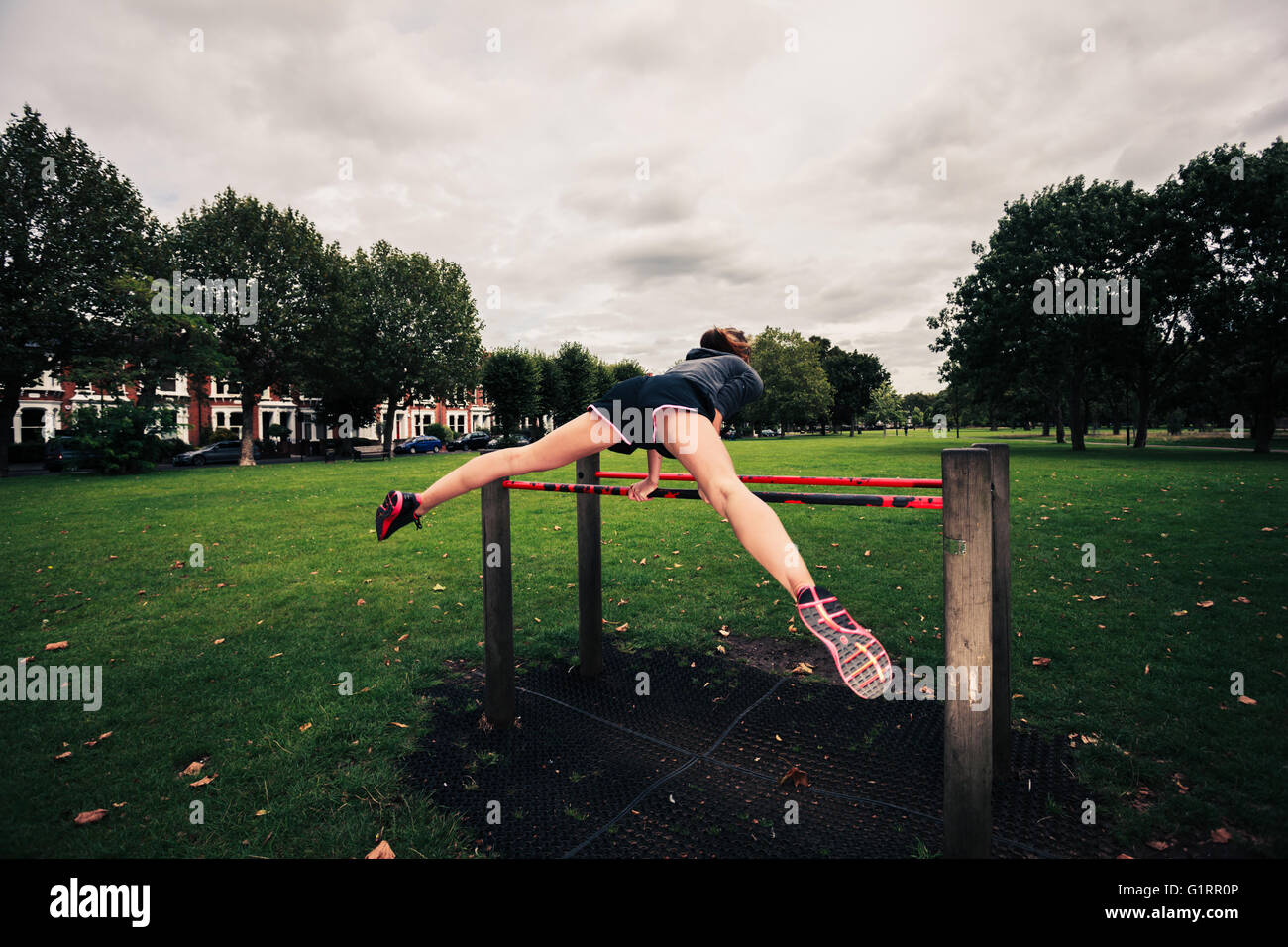 A woman is doing a planche on fitness equipment in the park - Stock Image