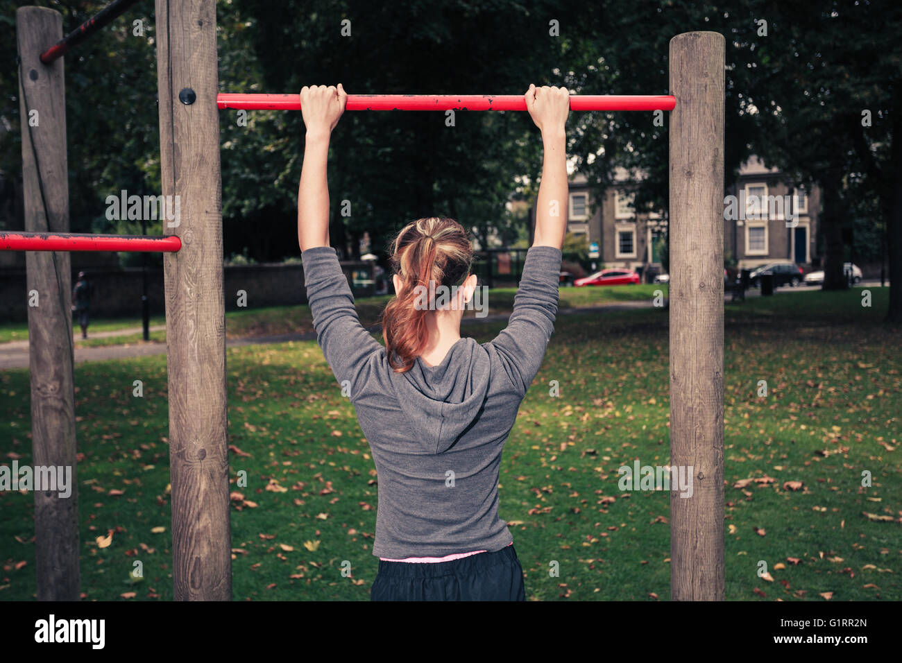 A young woman is doing pullups in the park - Stock Image
