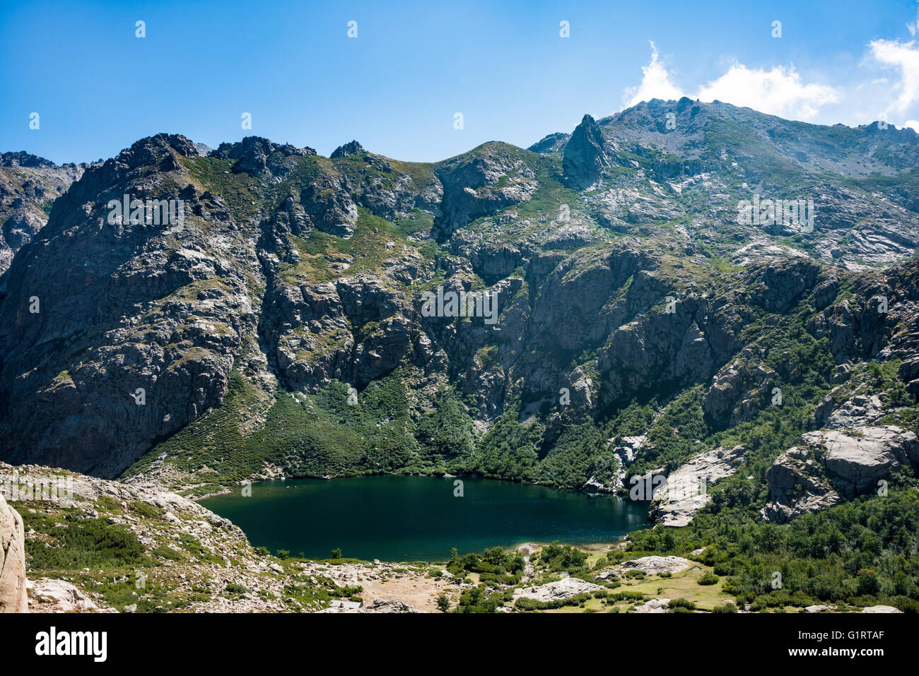 Mountain lake Lac de Melo, view from the Lac de Capitello, mountains in background, Restonica high valley - Stock Image