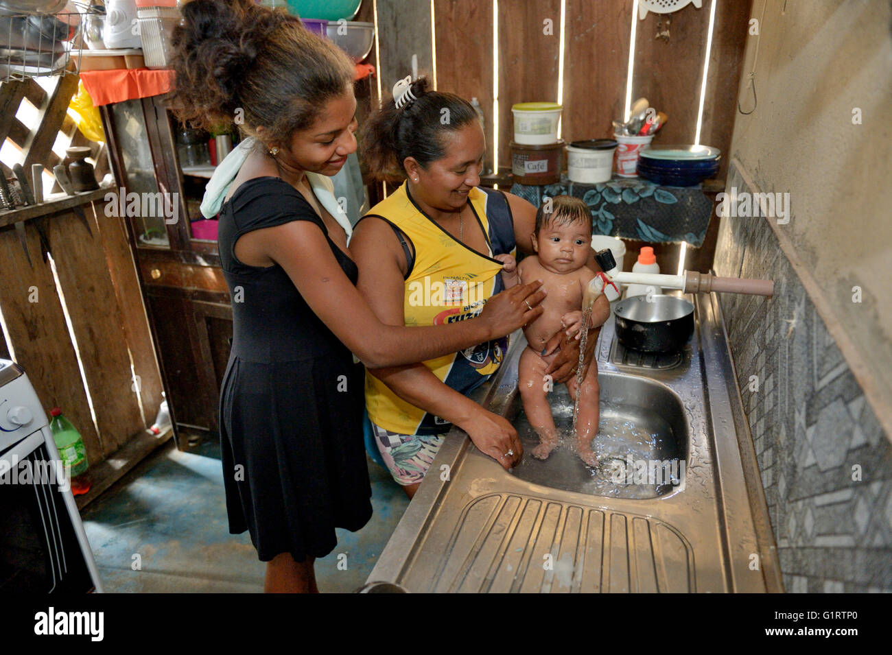 Women washing a baby in the sink of a kitchen, fishing village Pimental, district Itaituba, Pará state, Brazil - Stock Image