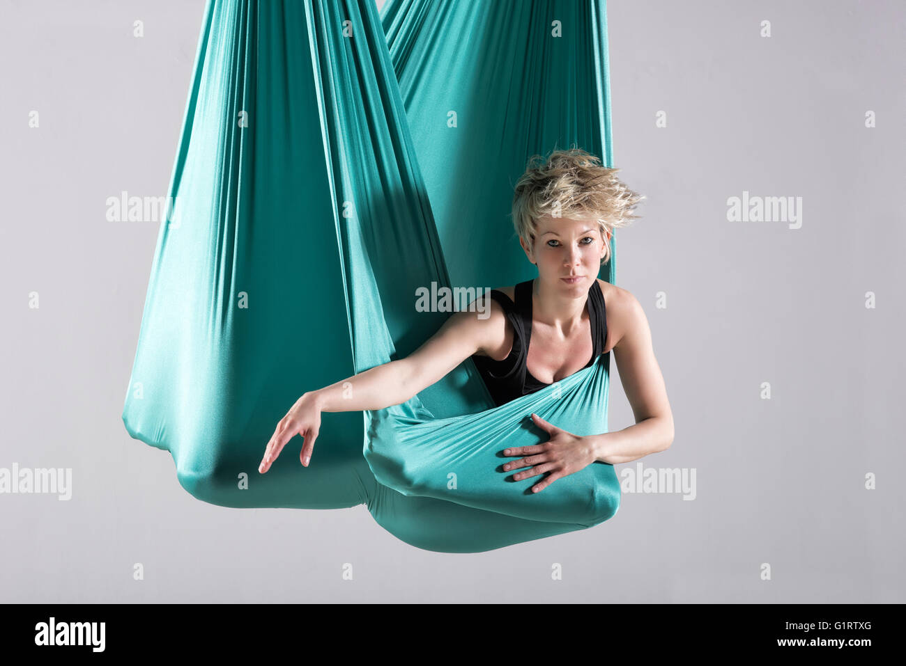 Single athletic woman doing intense leg and hip stretching exercises wrapped in aerial yoga blanket suspended from - Stock Image