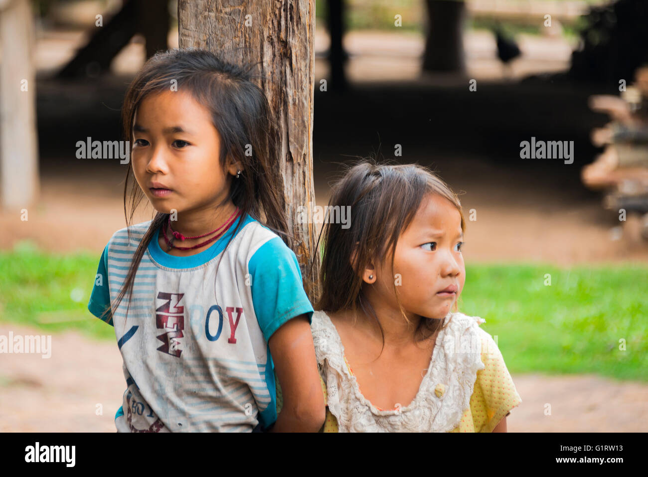 Two shy girls by a post of a hut, Ban Nalan Tai, Khmu Minority Village, Nam Ha National Park, Luang Namtha, Laos - Stock Image