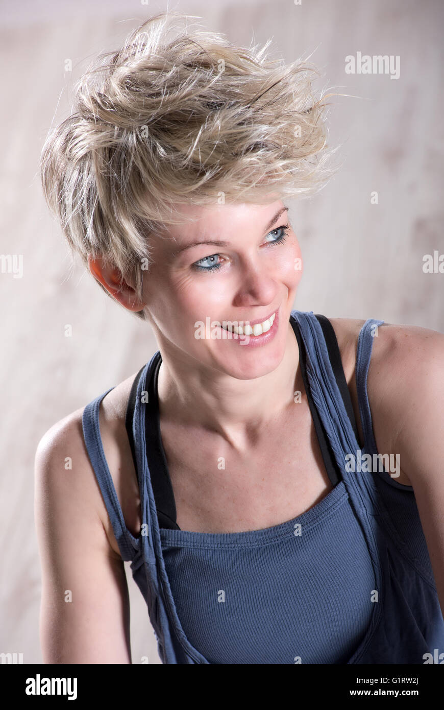 Portrait of single athletic beautiful blond woman smiling and looking sideways over stone marble background - Stock Image