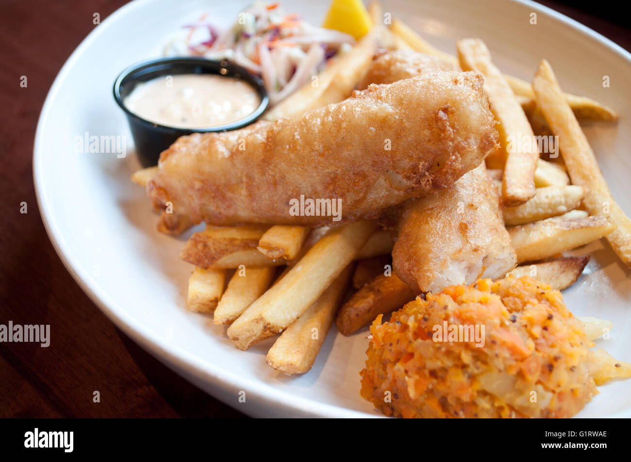 A beautiful prepared fish and chips platter, complete with coleslaw, clapshot and homemade tartar sauce. - Stock Image