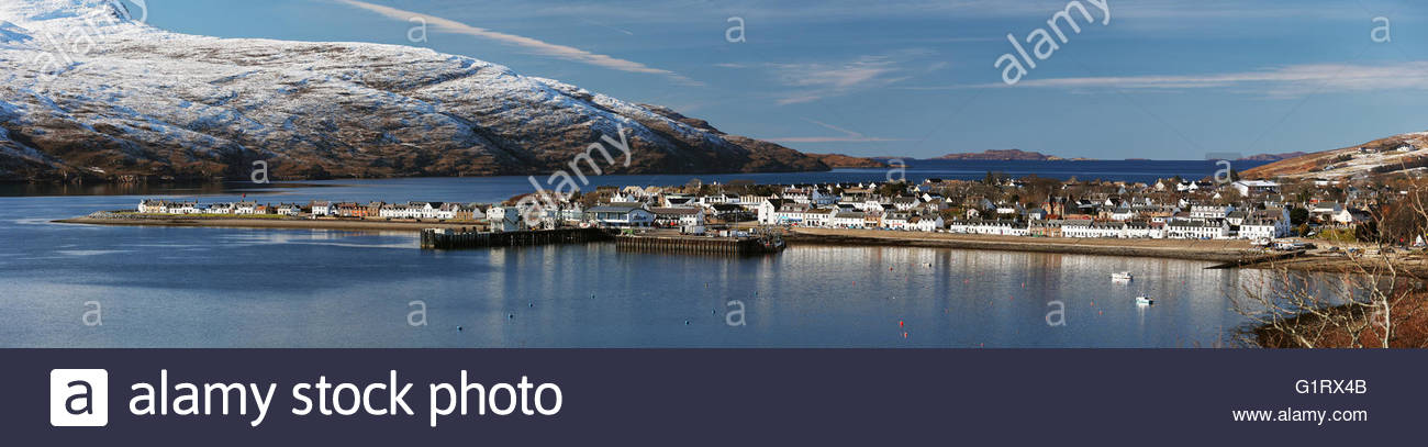 A panoramic image of the town of Ullapool on the north west coast of scotland, photographed on a sunny winter day. - Stock Image