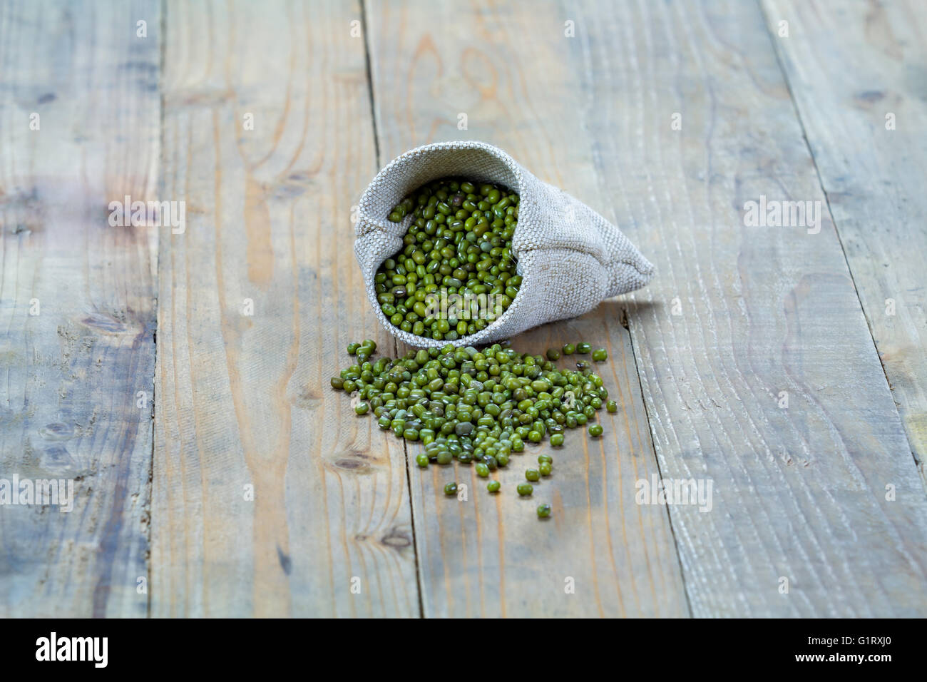 Mung beans in sack on vintage wooden boards - Stock Image