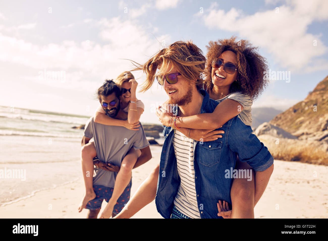 Two happy young men giving their girlfriends piggyback rides. Group of young people enjoying themselves during summertime - Stock Image