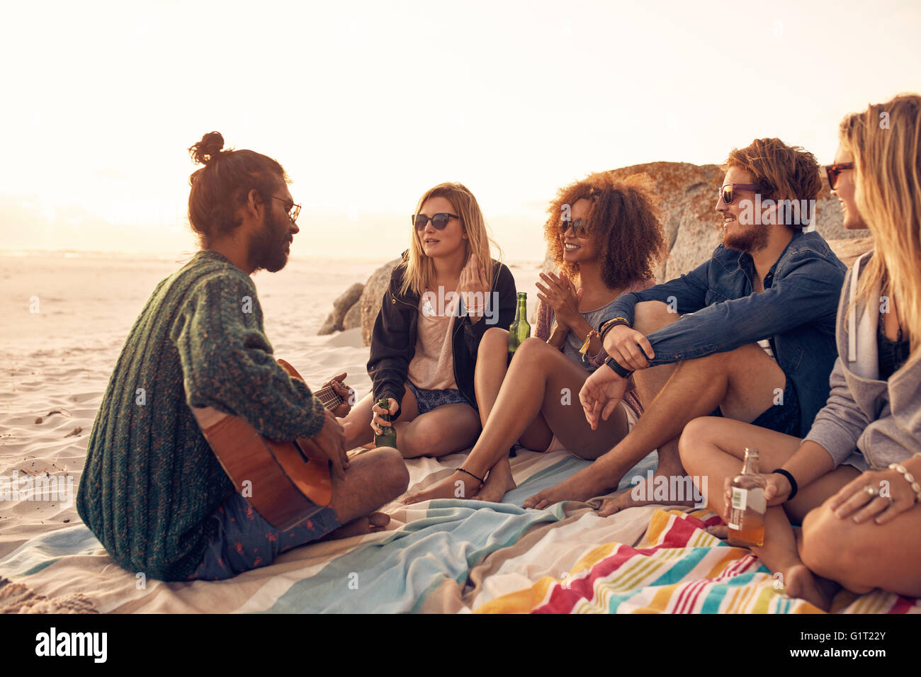 Group of friends relaxing at a sunset beach party with young man playing a guitar. Young people having a party on - Stock Image