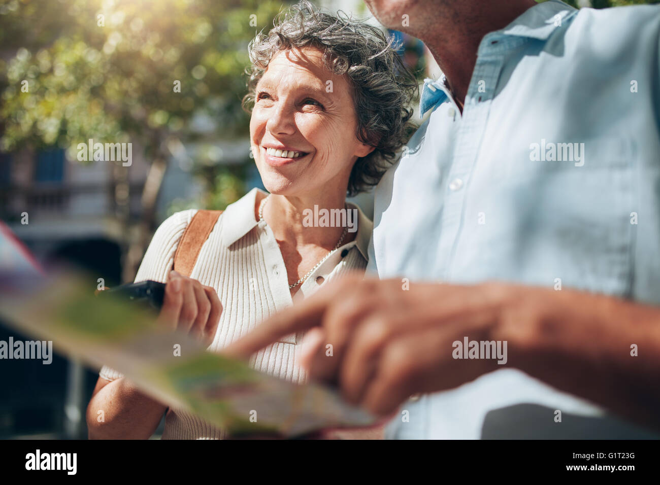 Senior woman with a man holding a city map. Happy and joyful, enjoying in retirement. - Stock Image