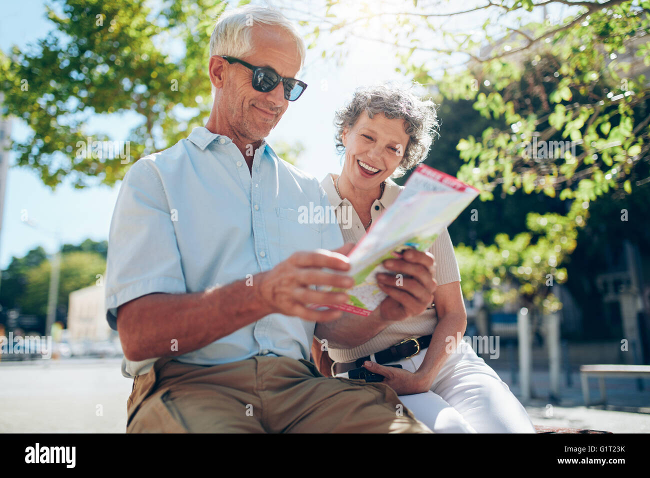 Elderly couple sitting outdoors in the city looking at a map. Happy senior man with his wife using city map. - Stock Image