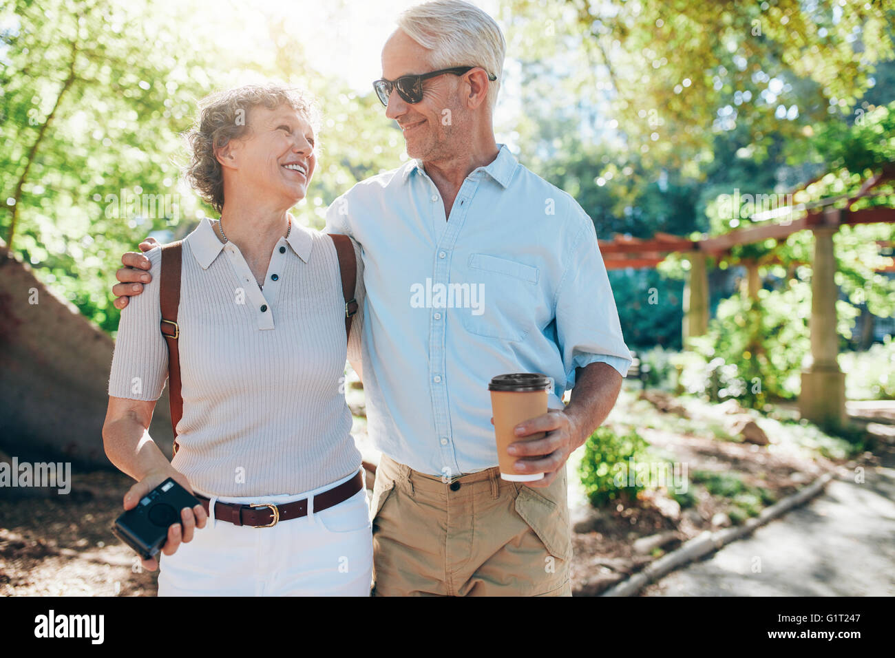 Portrait of happy mature couple walking together in a park. Husband and wife on a vacation. - Stock Image