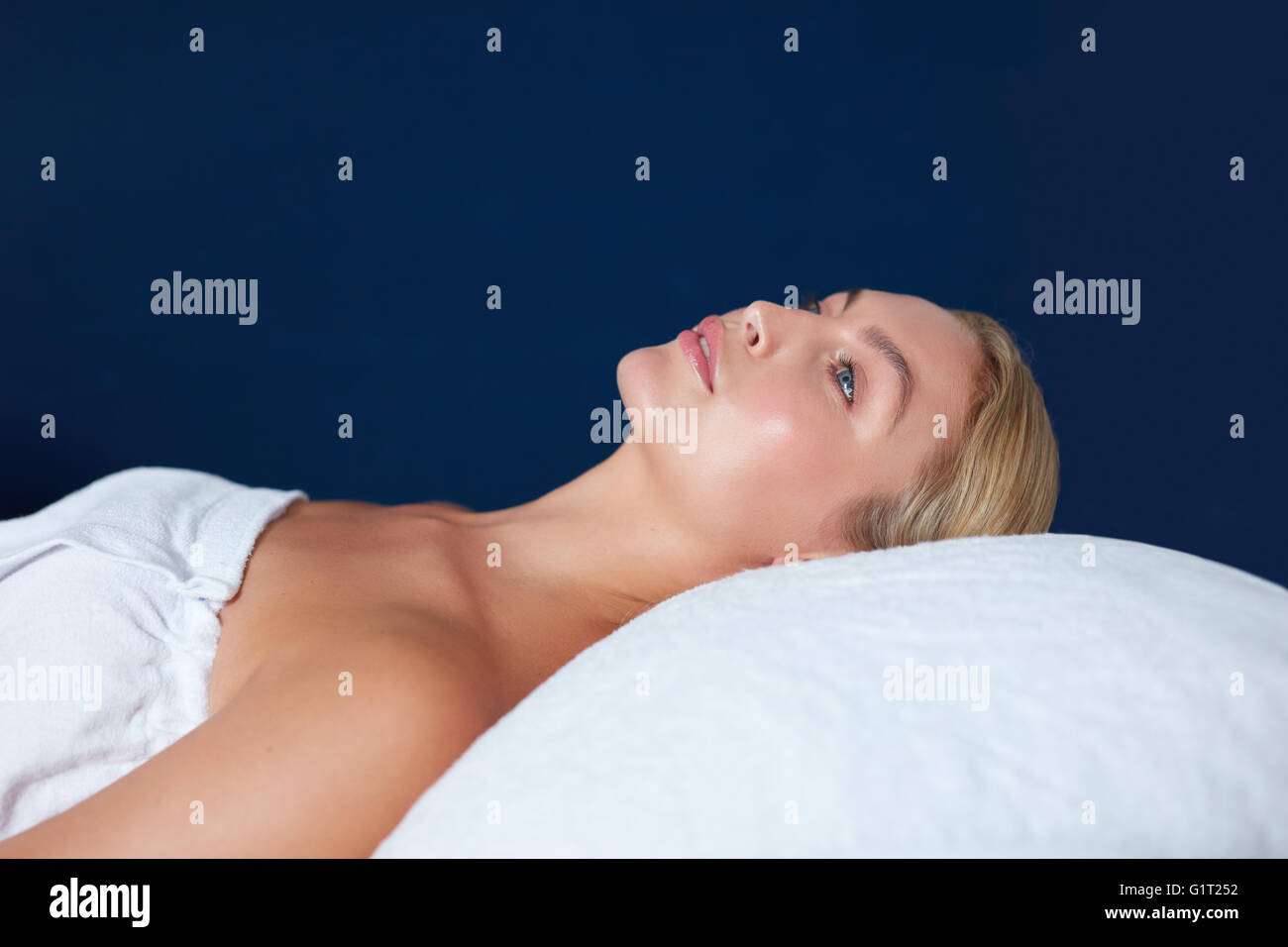 Side view shot of young woman lying on massage bed. Beautiful woman waiting for her spa treatment to begin. - Stock Image