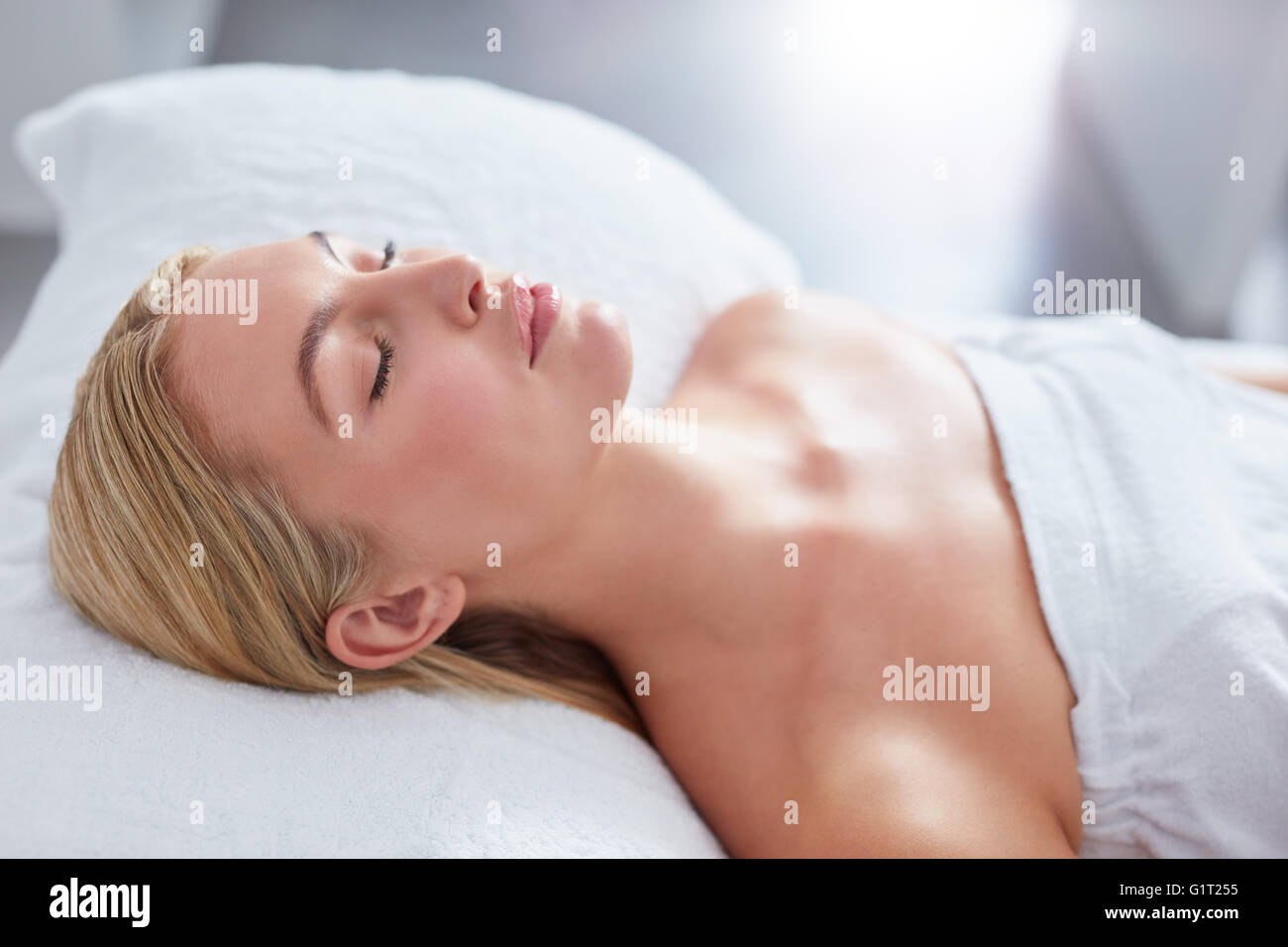 Close up of attractive woman at dayspa. She is lying on massage table. Beauty and health concept. - Stock Image