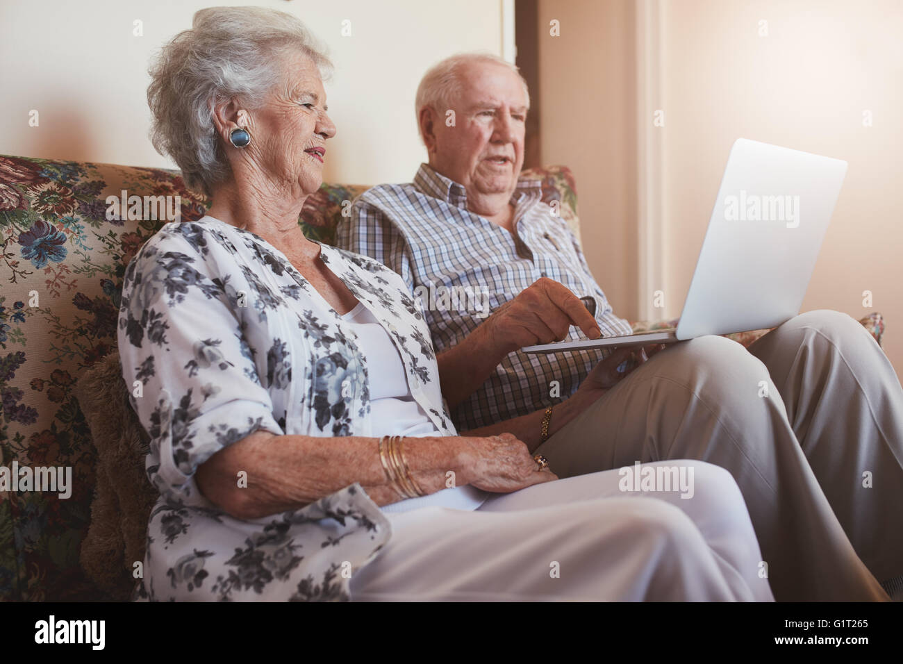 Indoor shot of senior couple sitting on a couch with a laptop computer. Old man and woman relaxing on a sofa using - Stock Image