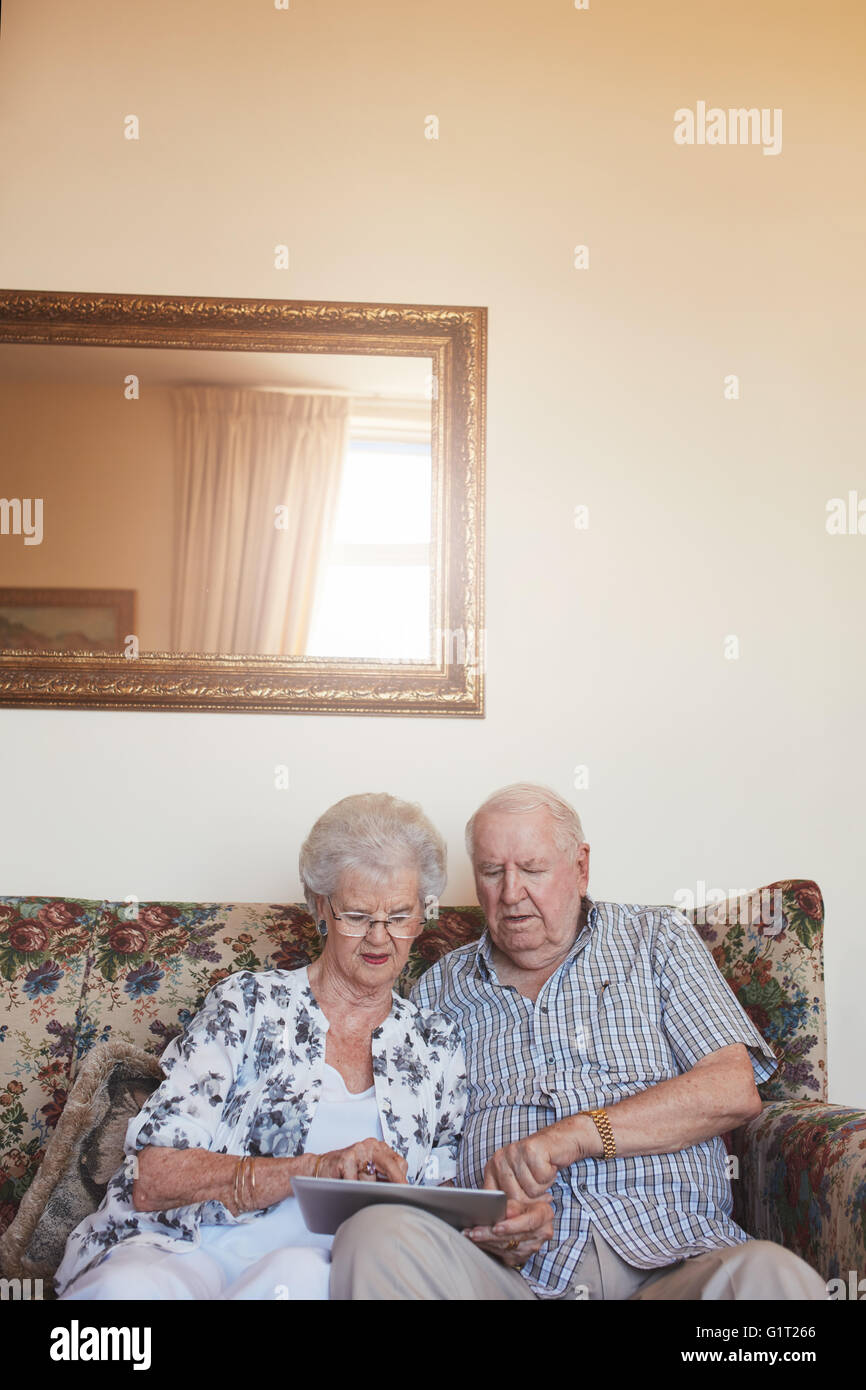 Vertical indoor shot of retired couple at home using digital tablet. Senior caucasian man and woman sitting together - Stock Image