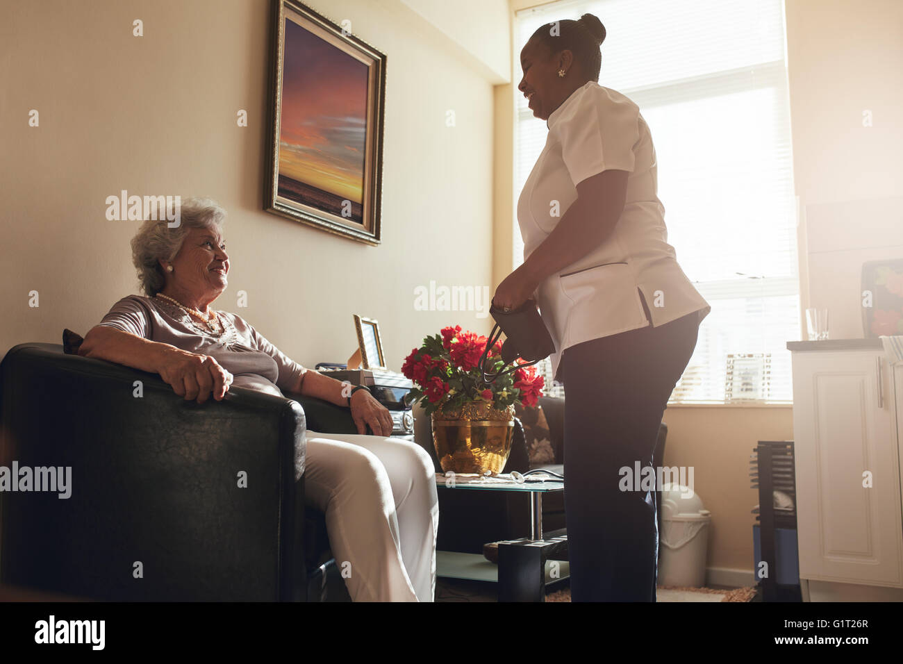 Senior woman sitting on a chair at home with female caregiver standing by. Female nurse visiting senior patient - Stock Image