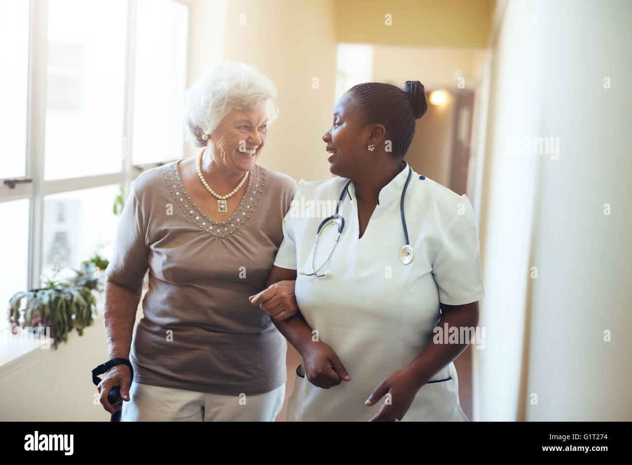Senior woman walking in the nursing home supported by a caregiver. Nurse assisting senior woman. - Stock Image