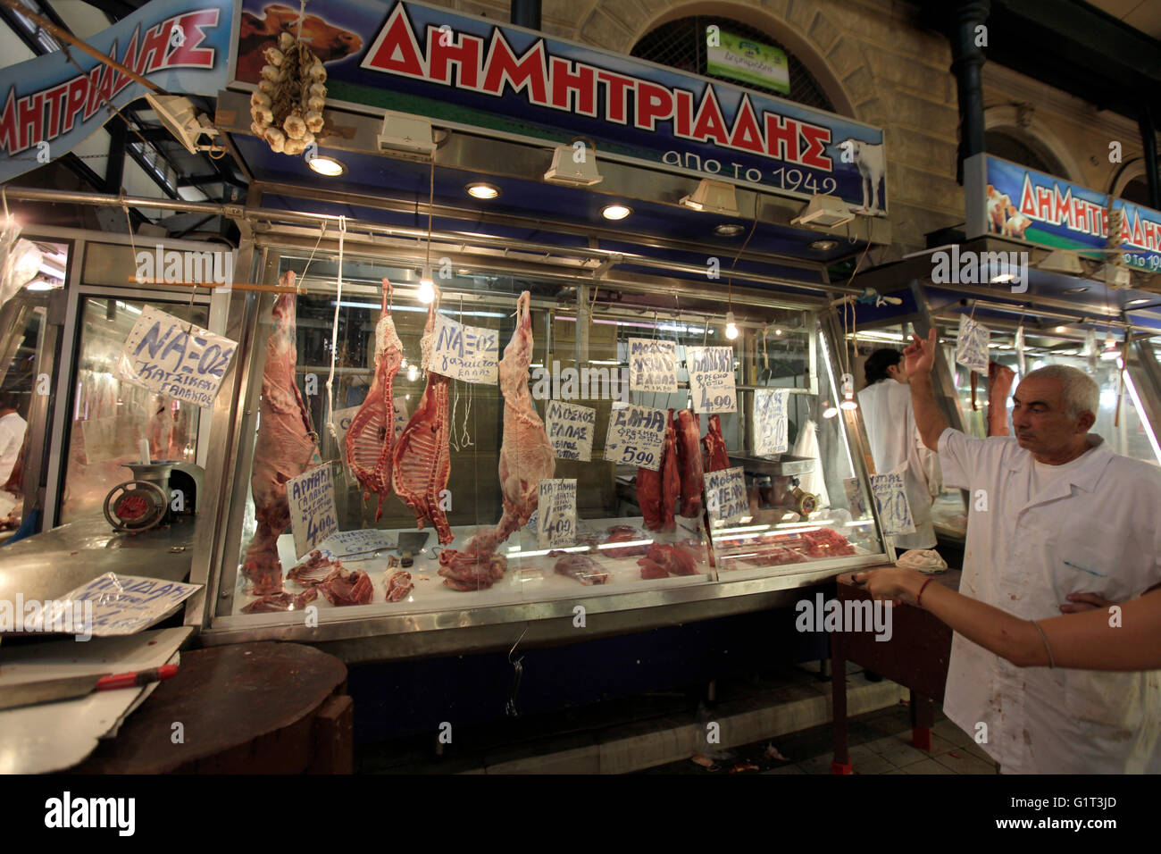 a meat seller/ vendor inside the central market or Athens Dimotiki Agora Public Market in Athens greece - Stock Image