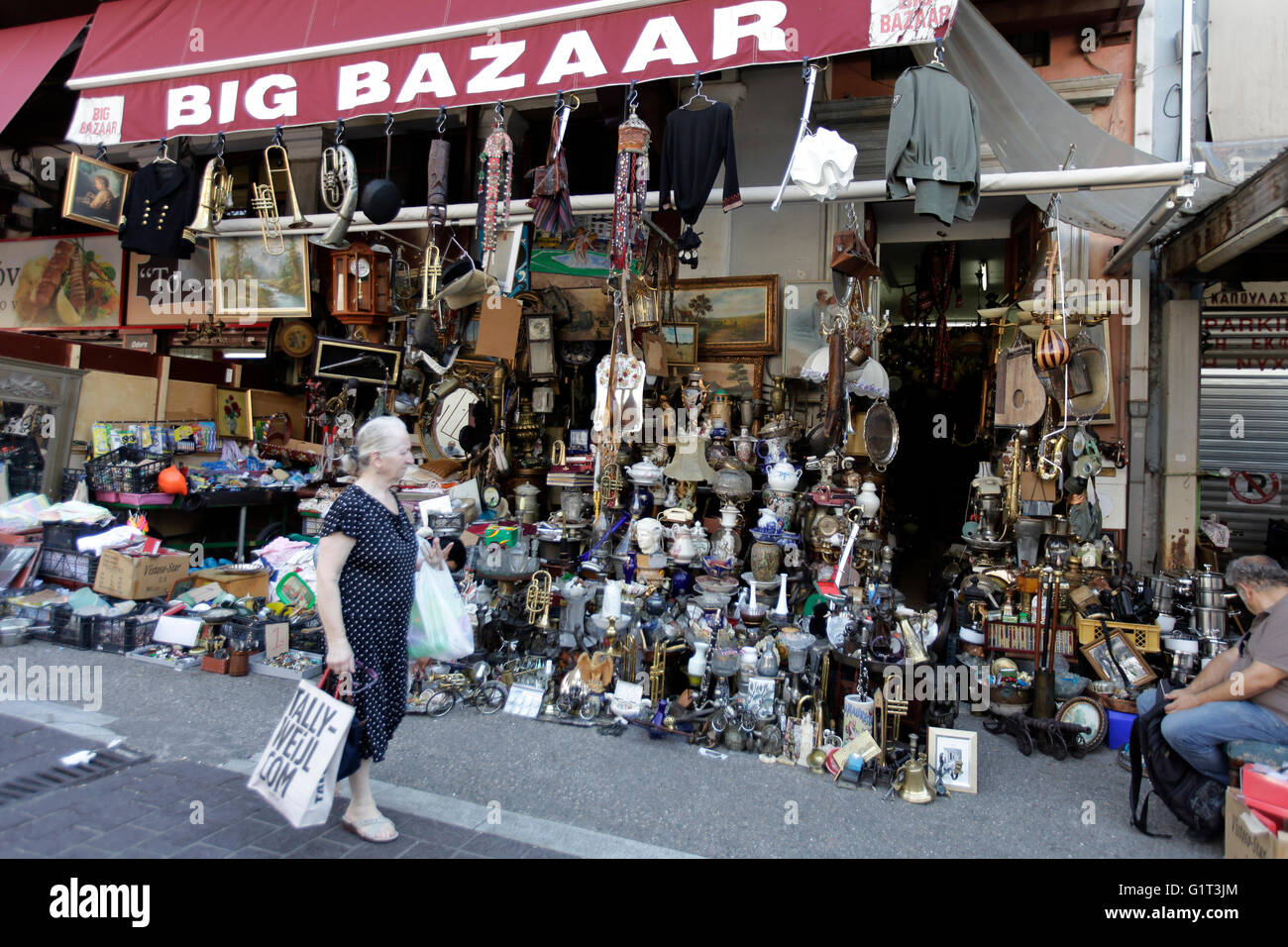 a woman walks past the big bazaar shop, in central athens , greece, selling Bric-à-brac, antiques and junk - Stock Image