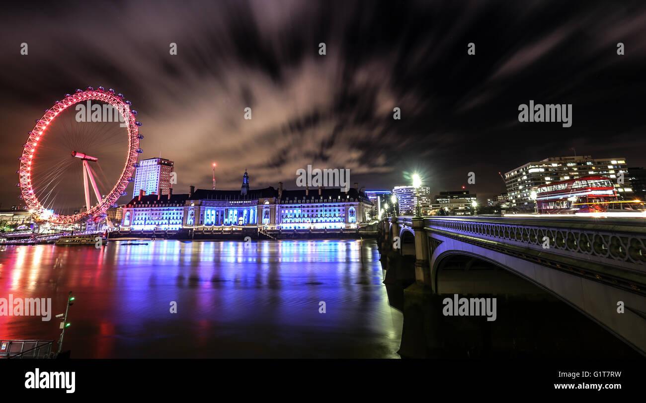 London Eye and Bridge across water at night time. Long exposure - Stock Image