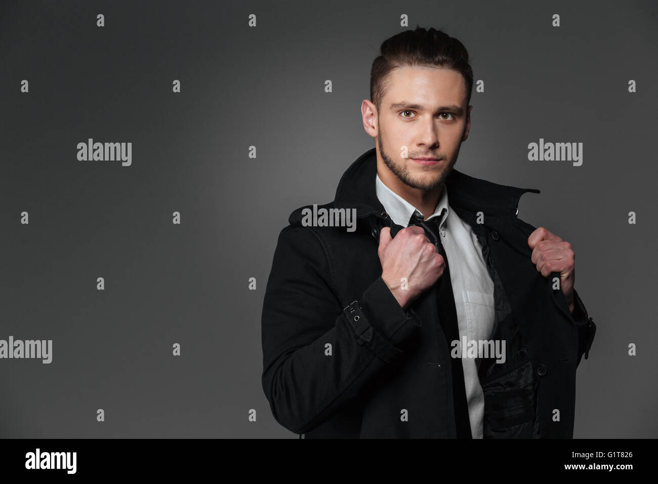 Closeup of handsome young businessman in black coat over grey background - Stock Image