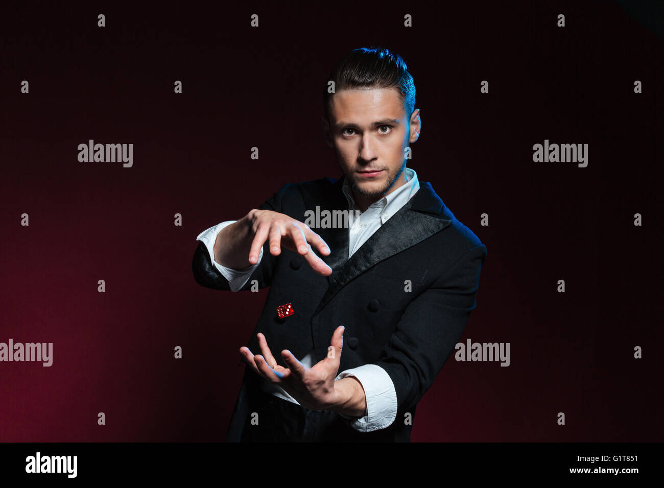 Confident young man magician showing tricks using one flying dice over dark background Stock Photo