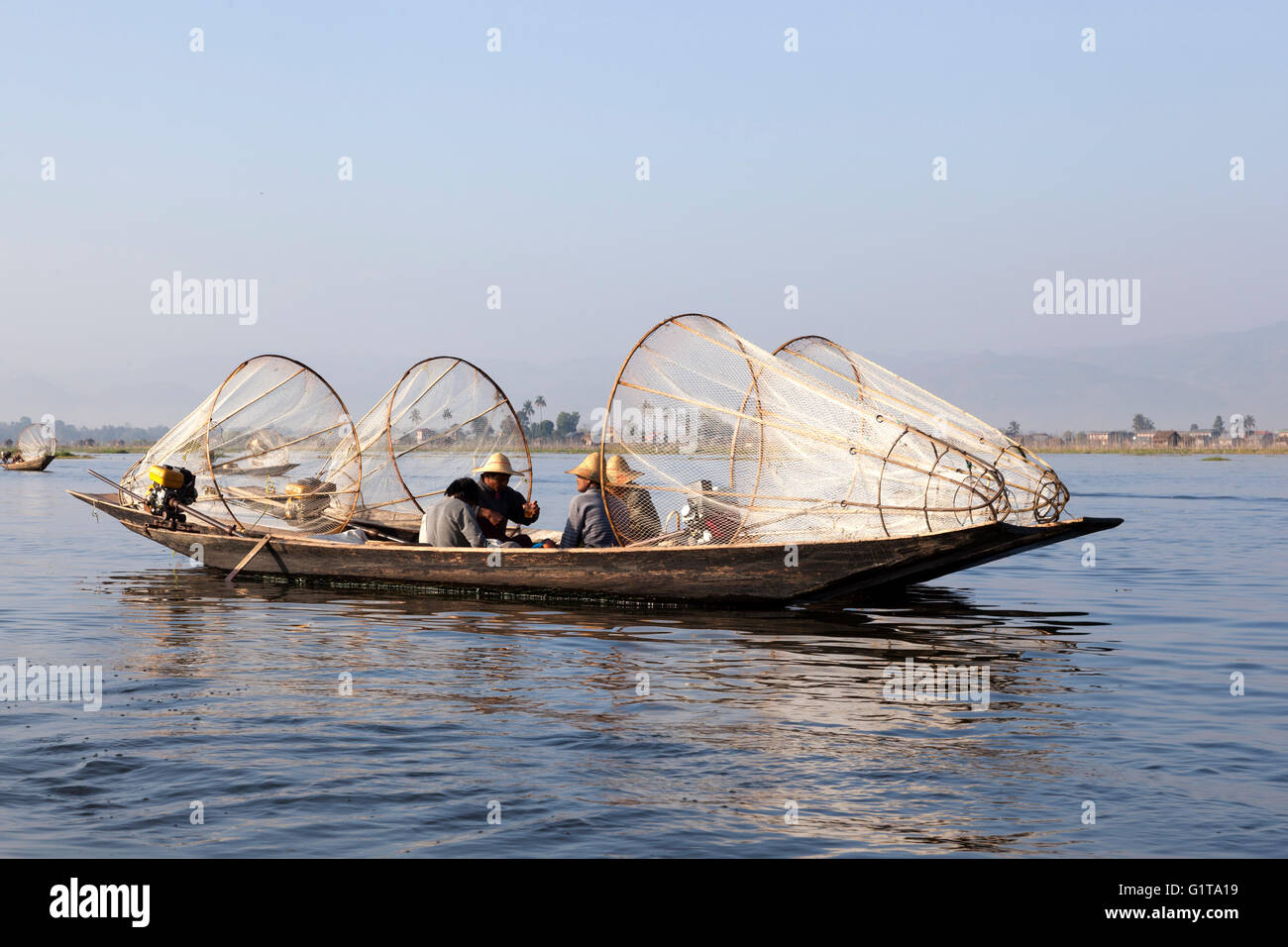 On the Inle Lake, two motorized pirogues anchored side by side with fishermen resting a while (Myanmar). - Stock Image
