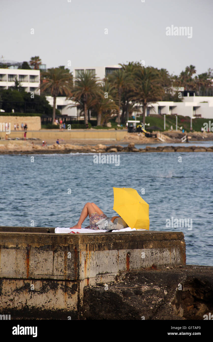 Someone sun bathing under a bright yellow umbrella on a concrete harbour - Stock Image
