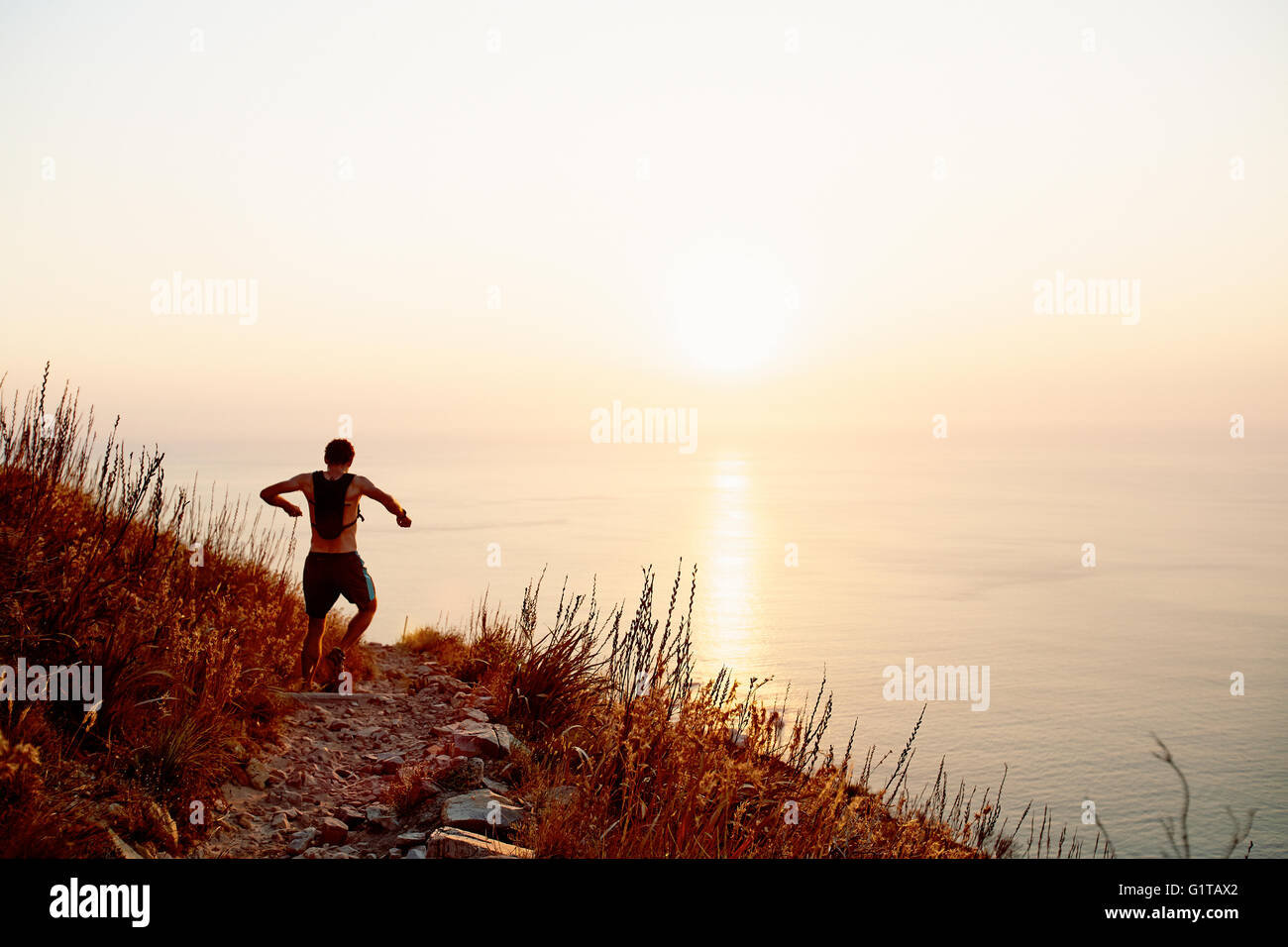 Male runner with backpack descending craggy trail overlooking sunset ocean - Stock Image