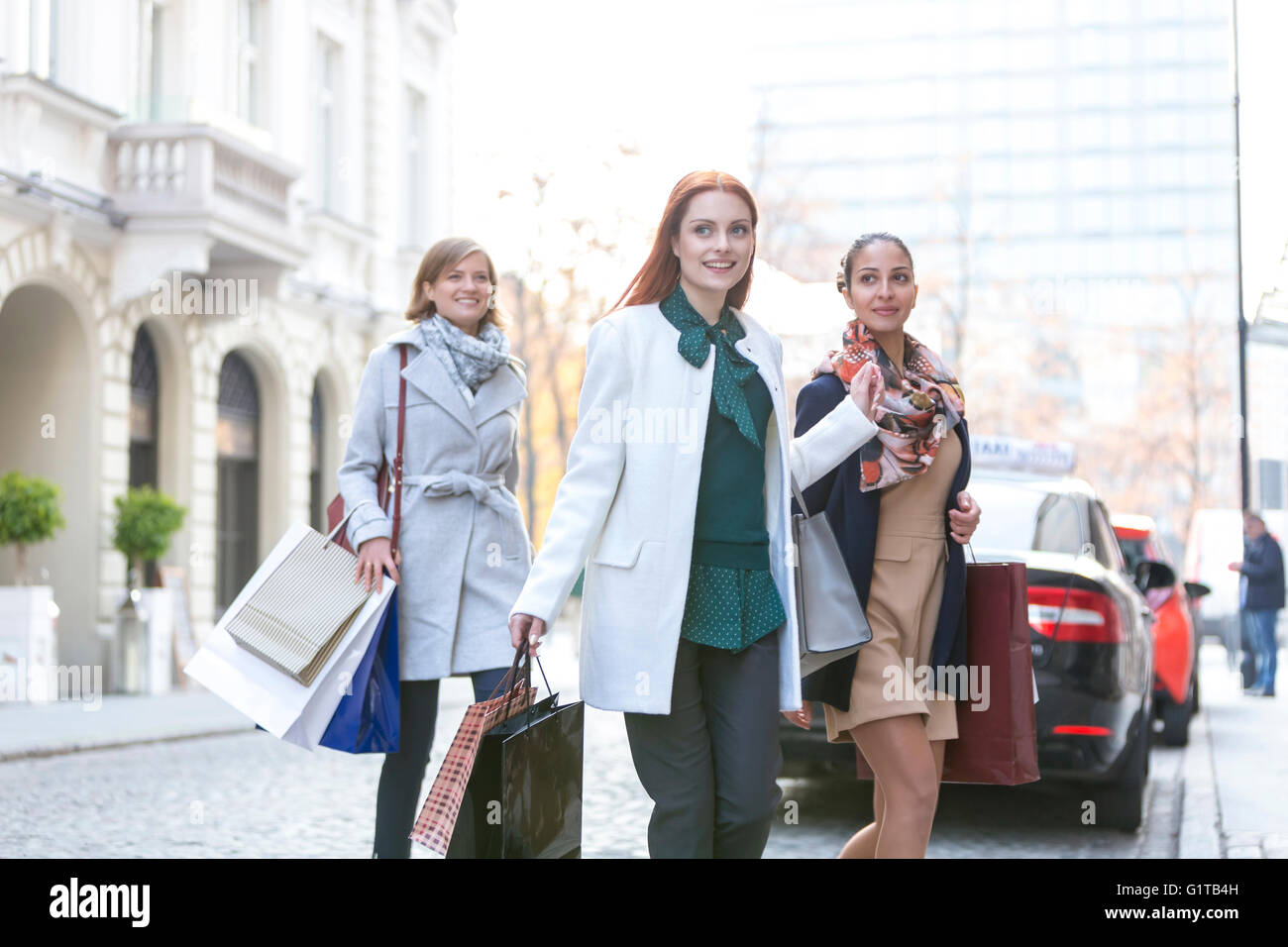 Smiling women with shopping bags crossing city street - Stock Image