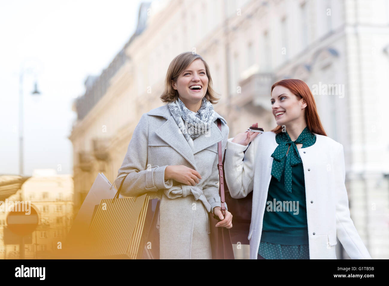 Smiling women carrying shopping bags in city Stock Photo