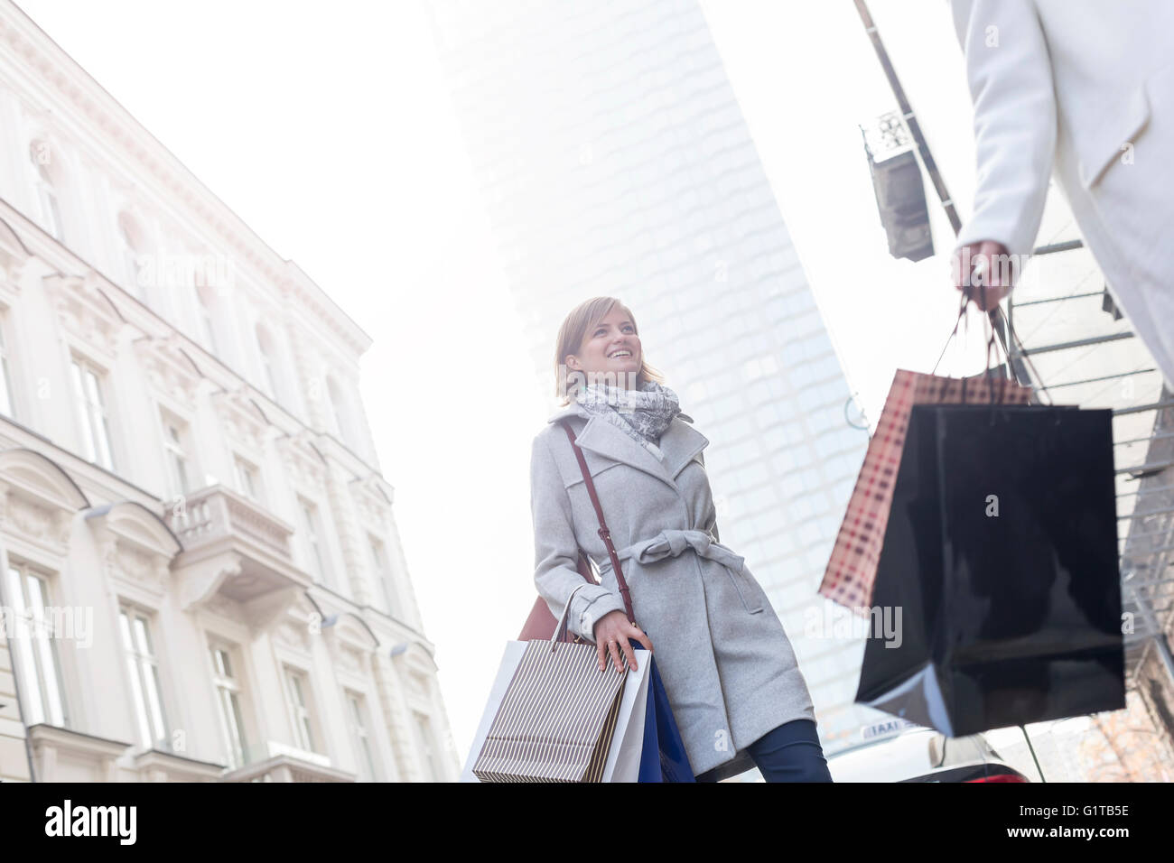 Women with shopping bags crossing city street below highrise - Stock Image