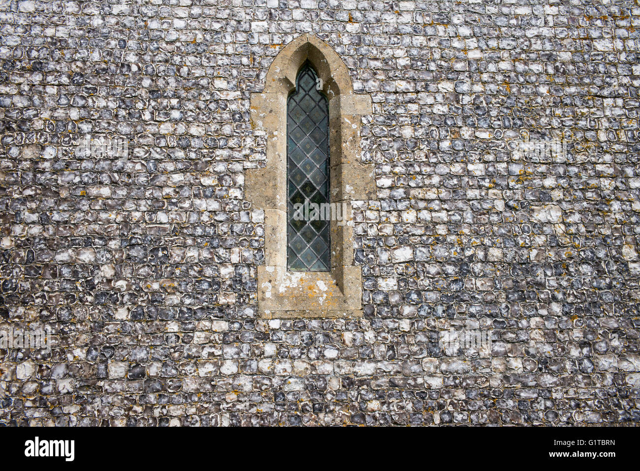 Vernacular architecture using flint stone for the walls and quarry stone window surrounds of St James's Church, - Stock Image