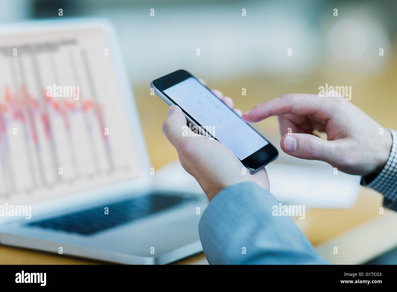 Close up of businessman dialing cell phone at laptop Stock Photo