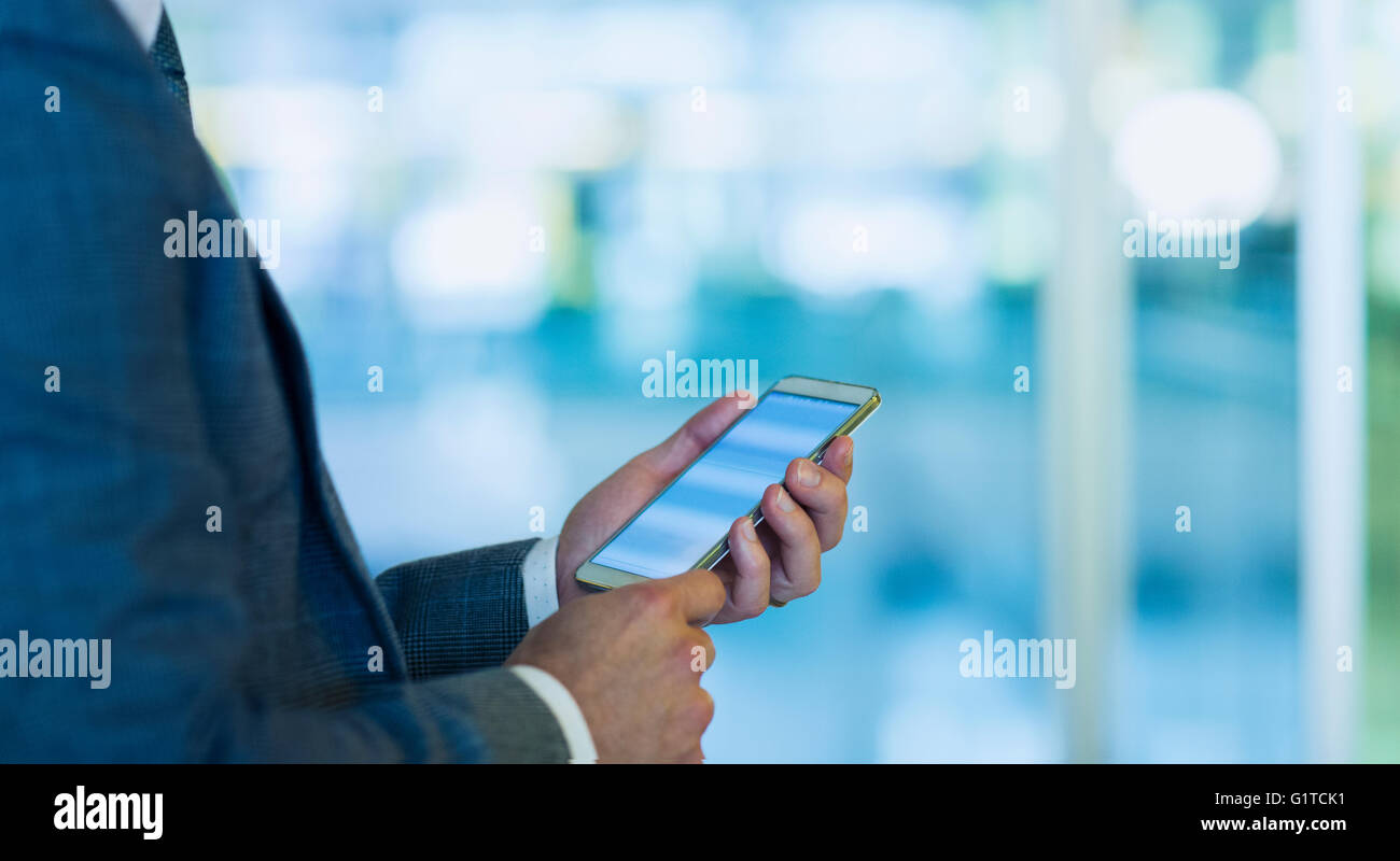 Businessman using cell phone in office - Stock Image