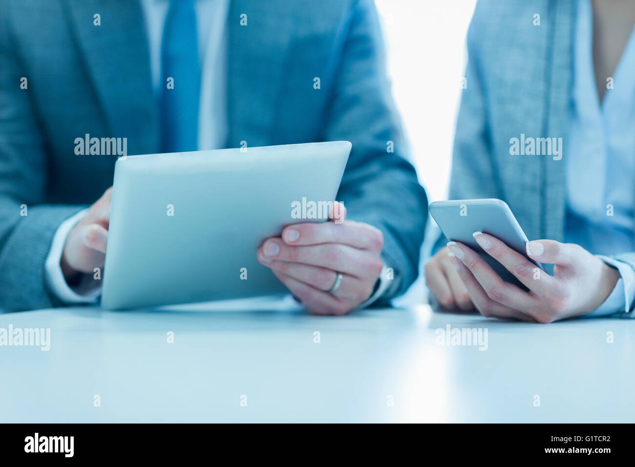 Businessman and businesswoman using digital tablet and cell phone - Stock Image