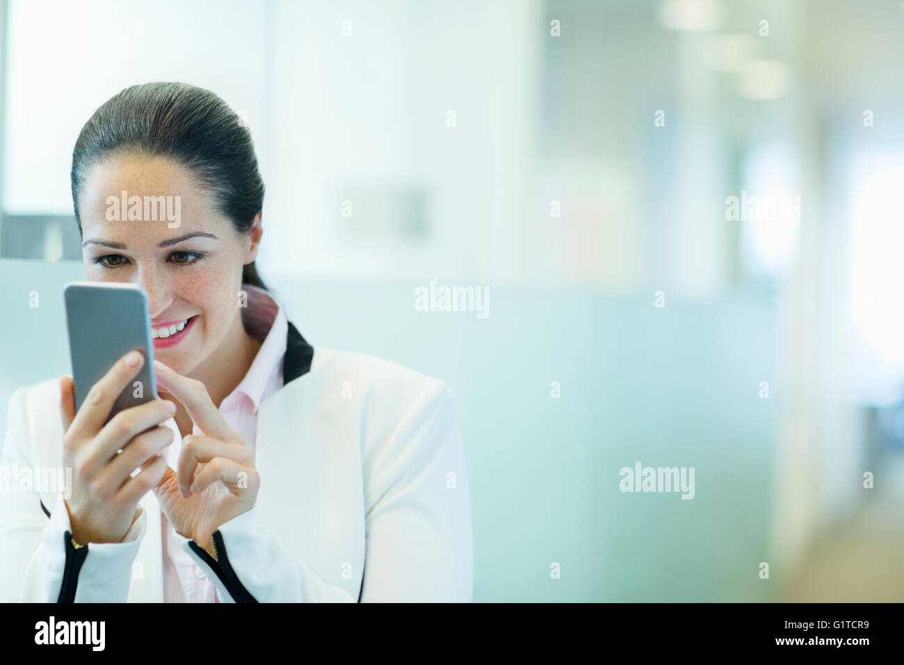 Smiling businesswoman using cell phone in office corridor - Stock Image