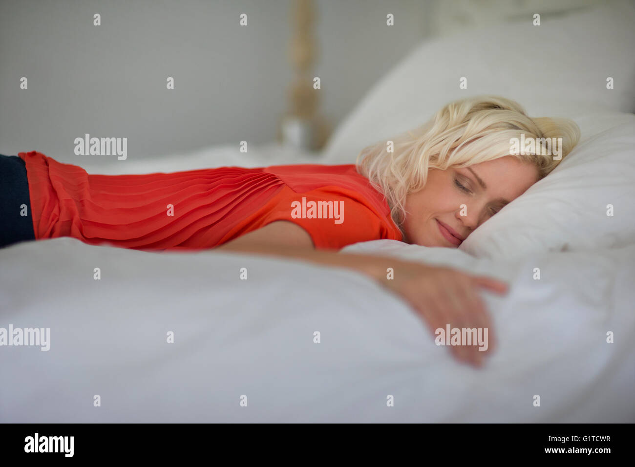 Serene woman sleeping on bed with eyes closed - Stock Image