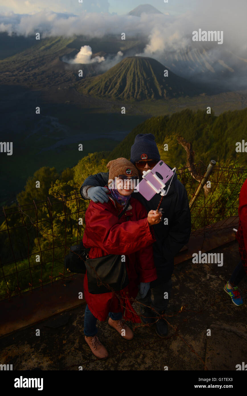 A couple taking a selfie with their smartphone and selfie stick in front of Bromo-Batok-Semeru volcanoes in Java, - Stock Image