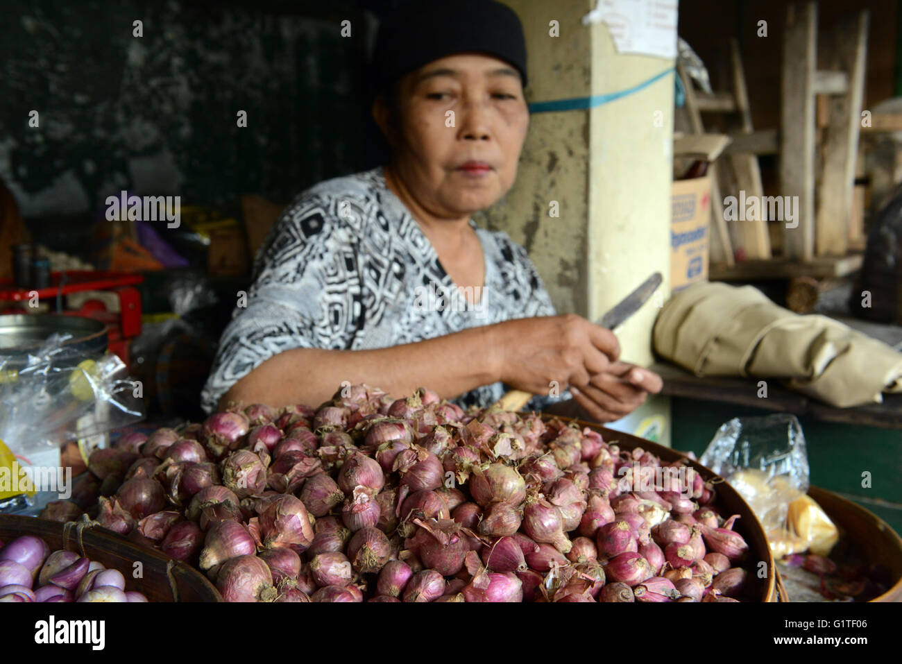A Javanese woman peeling shallots in a market in Yogyakarta. - Stock Image