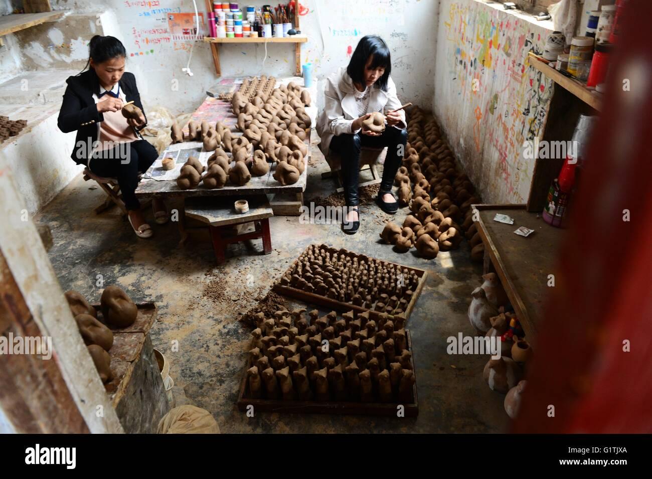 (160519) -- ZHENGZHOU, May 19, 2016 (Xinhua) -- Craftswomen work on clay sculptures at a workshop in Yangqitun Village - Stock Image