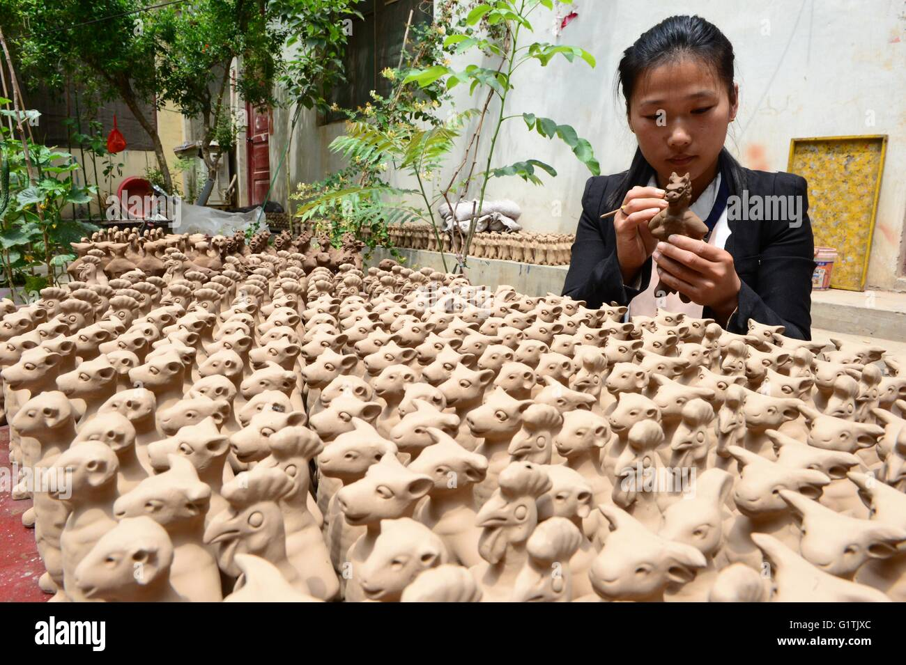 (160519) -- ZHENGZHOU, May 19, 2016 (Xinhua) -- A craftswoman works on a clay sculpture at her workshop in Yangqitun - Stock Image