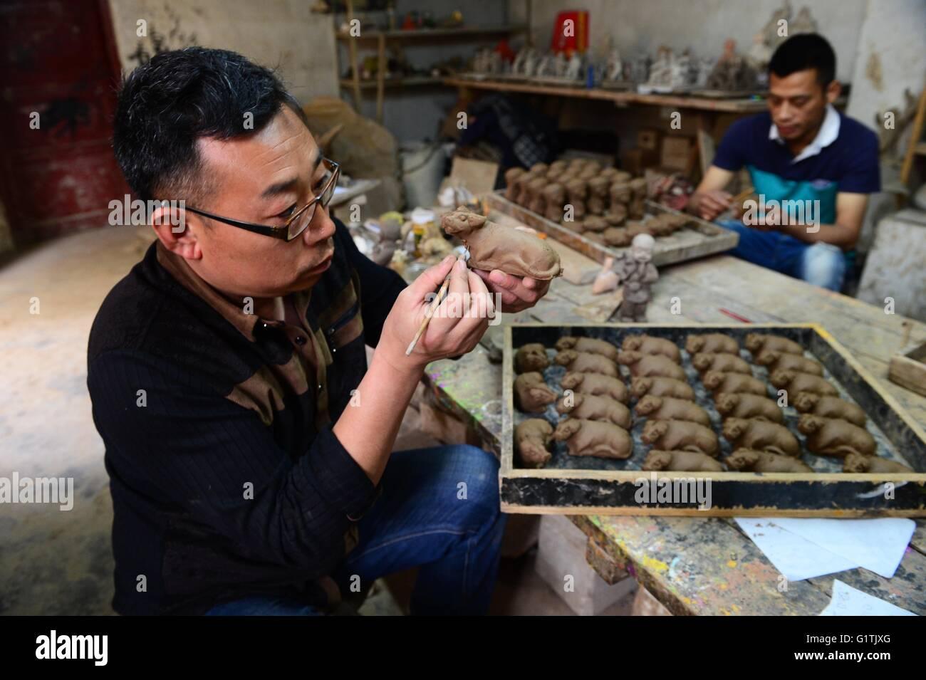 (160519) -- ZHENGZHOU, May 19, 2016 (Xinhua) -- Craftsmen work on clay sculptures at a workshop in Yangqitun Village - Stock Image