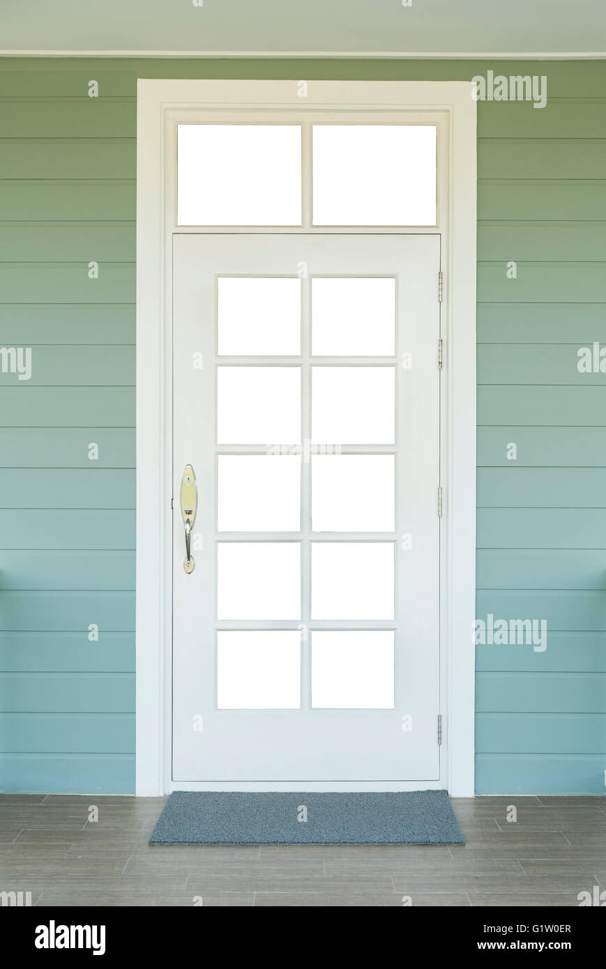 vintage white door on the green wall with a gray carpet - Stock Image
